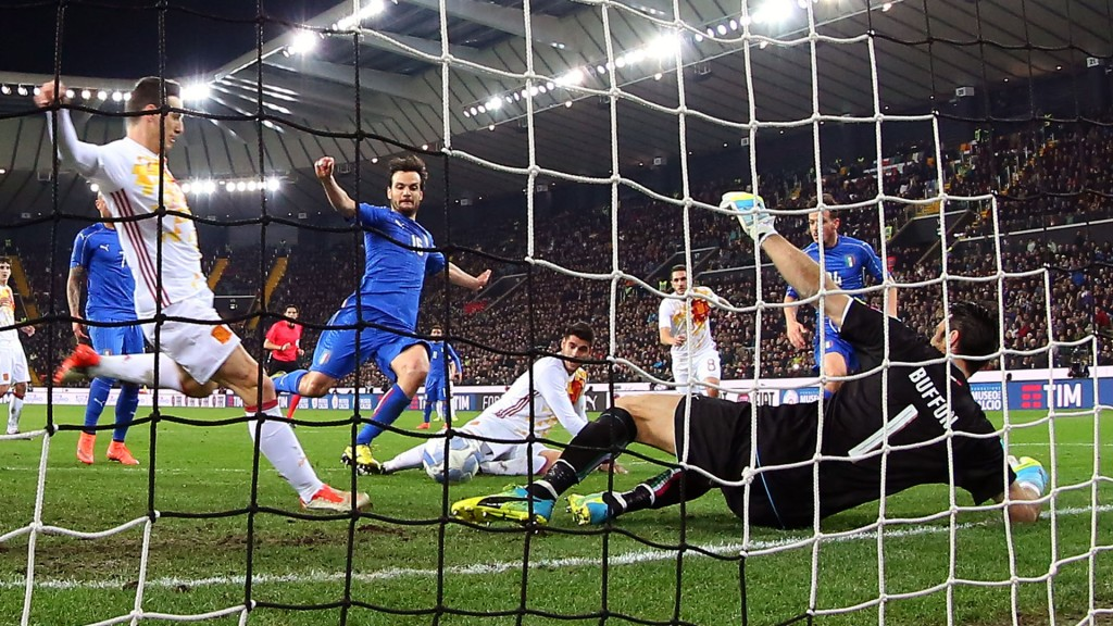 Spain's Aritz Aduriz, left, scores past Italy's goalkeeper Gianluigi Buffon, right, during a friendly soccer match between Italy and Spain, at the Friuli Dacia Arena stadium in Udine, Italy, Thursday, March 24, 2016. Two-time defending champion Spain began its preparations for this summer's European Championship with a 1-1 draw against Italy in a friendly on Thursday. (AP Photo/Paolo Giovannini)